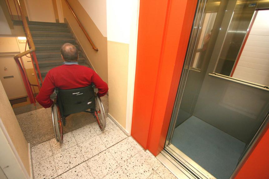 Mann i rullestol som har stoppet foran en trapp etter å ha kommet ut av en heis (Foto: Colourbox.com)