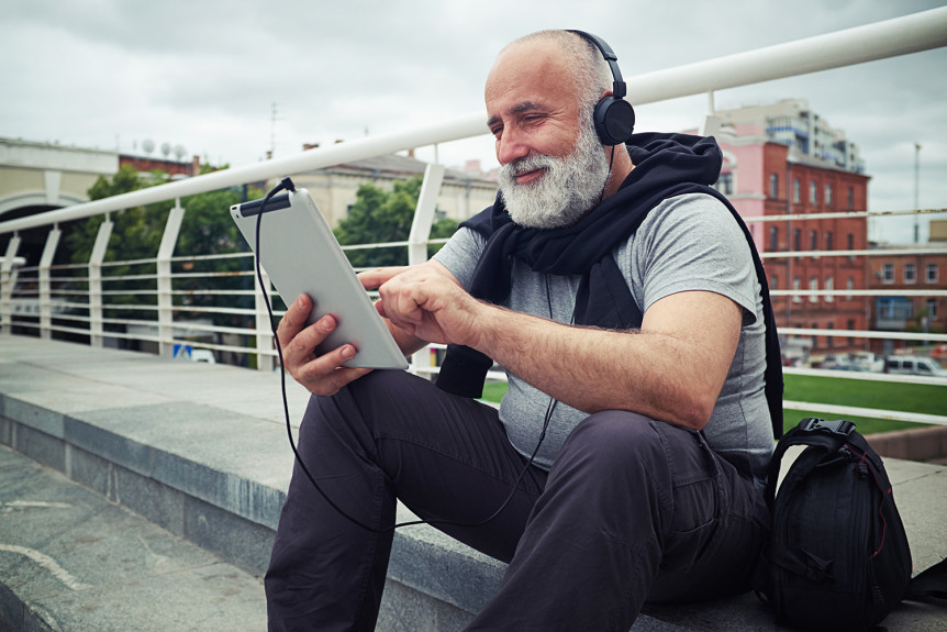 Stylish aged man in headphones is sitting on a sidewalk of the bridge on a cloudy day with tablet computer and smiling