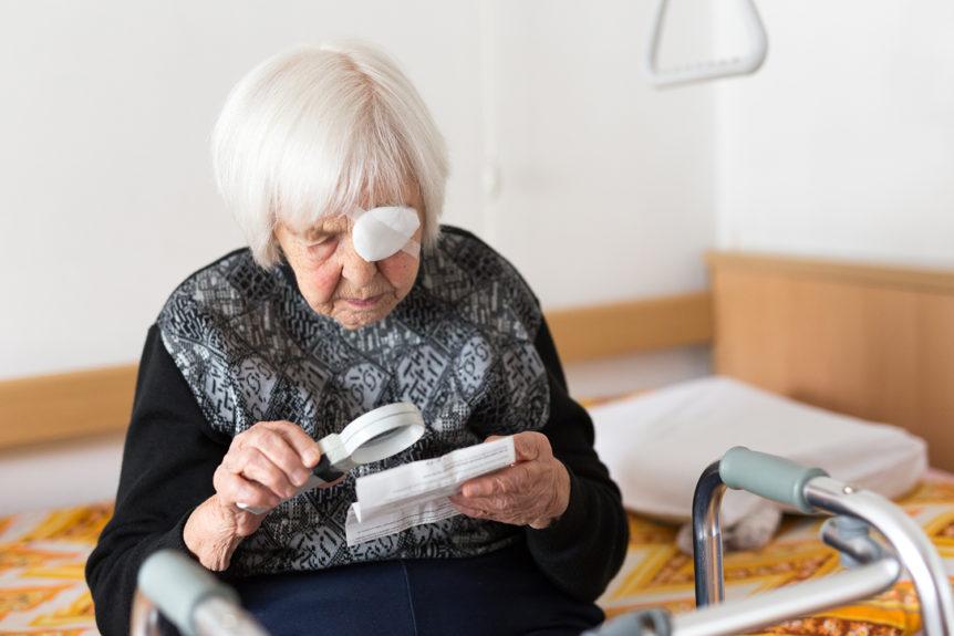 Eldre dame med bind for det venstre øyet som sitter på sengen og bruker lupe for å lese (Foto: Colourbox.com)