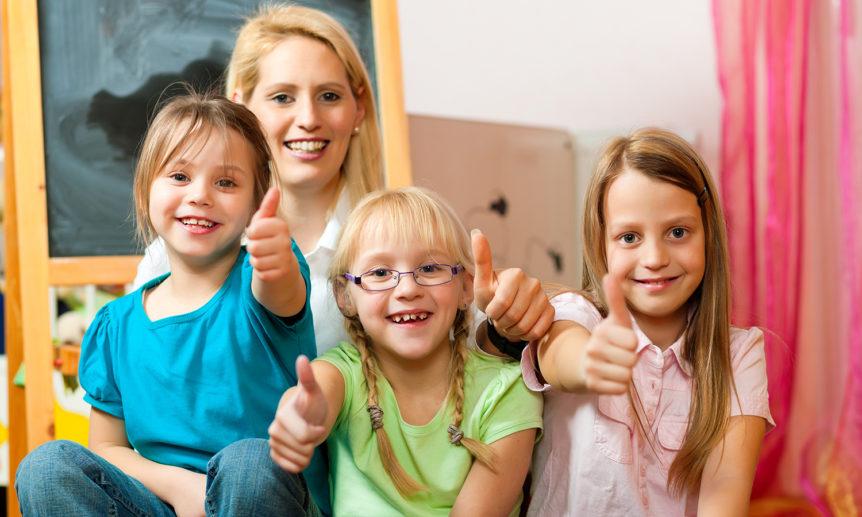 Tre smilende barn som viser tommel opp og en voksen som sitter bak dem i et klasserom (Foto: colourbox.com)