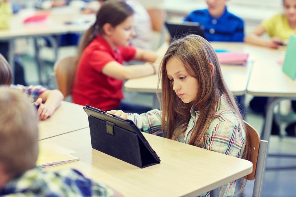 En jente som ser på nettbrett mens hun sitter ved pulten i klasserommet (Foto: colourbox.com)