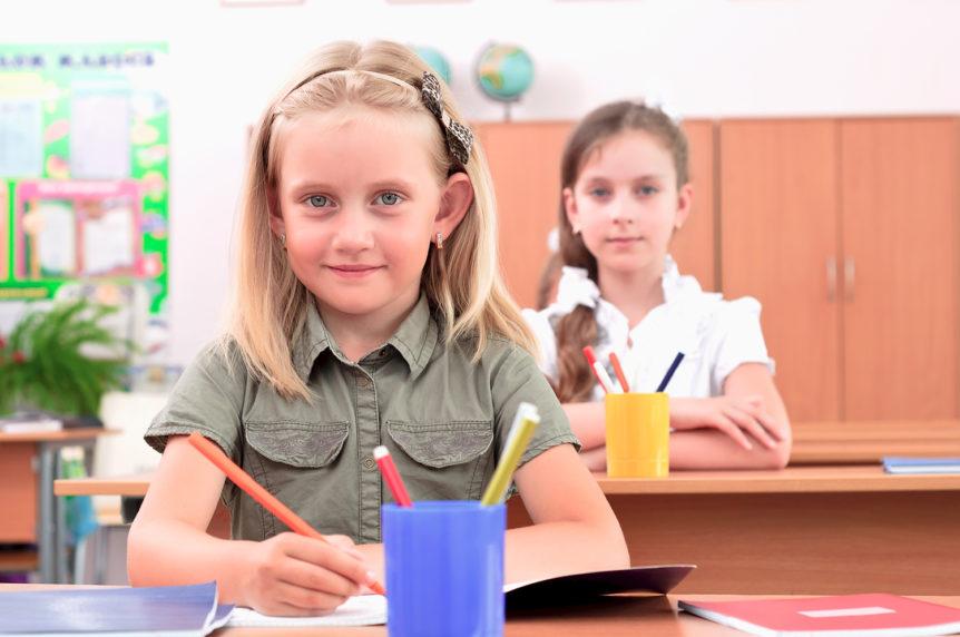 To elever som sitter ved pultene sine i et klasserom (Foto: Colourbox)