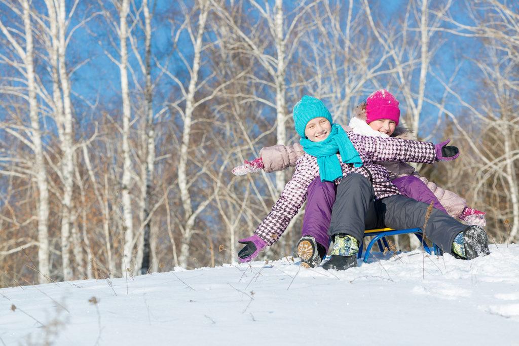 To glade barn som sitter på en kjelke på vinteren (Foto: colourbox.com)