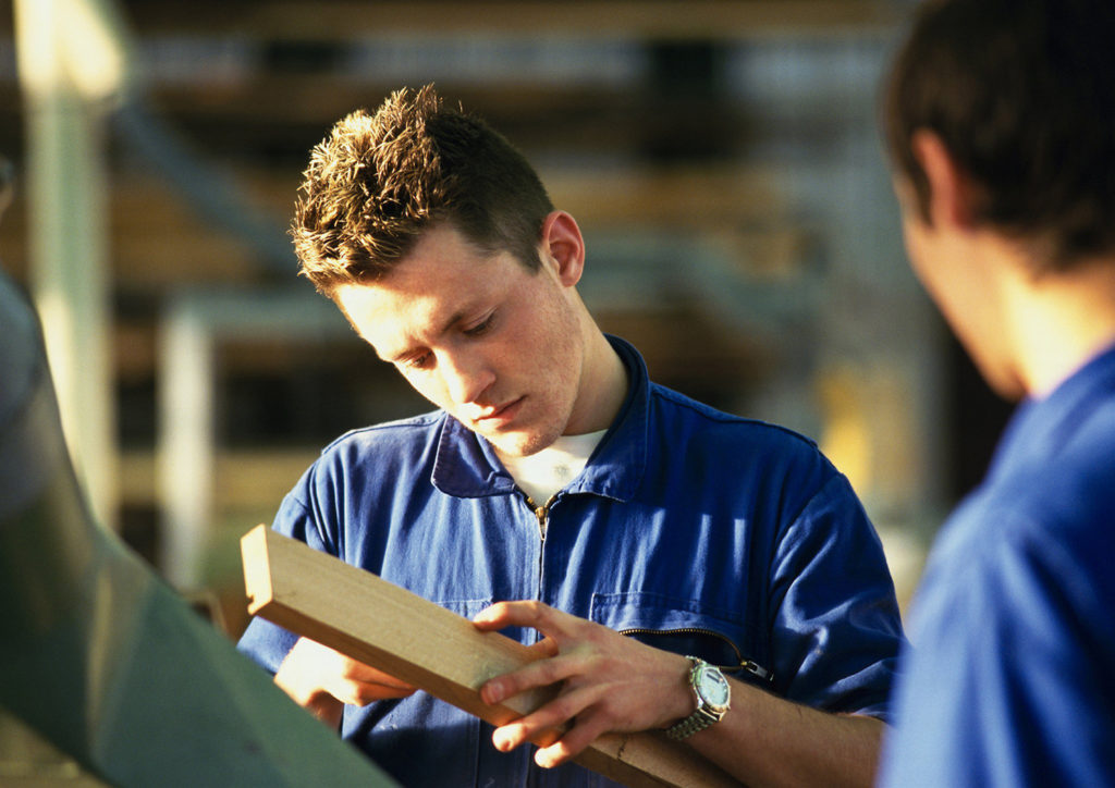 Ung mann i blå arbeidsjakke som måler en planke (Foto: colourbox.com)