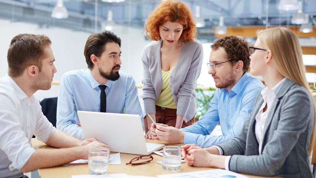 Fem voksne mennesker som sitter rundt etter bord (Foto: colourbox.com)