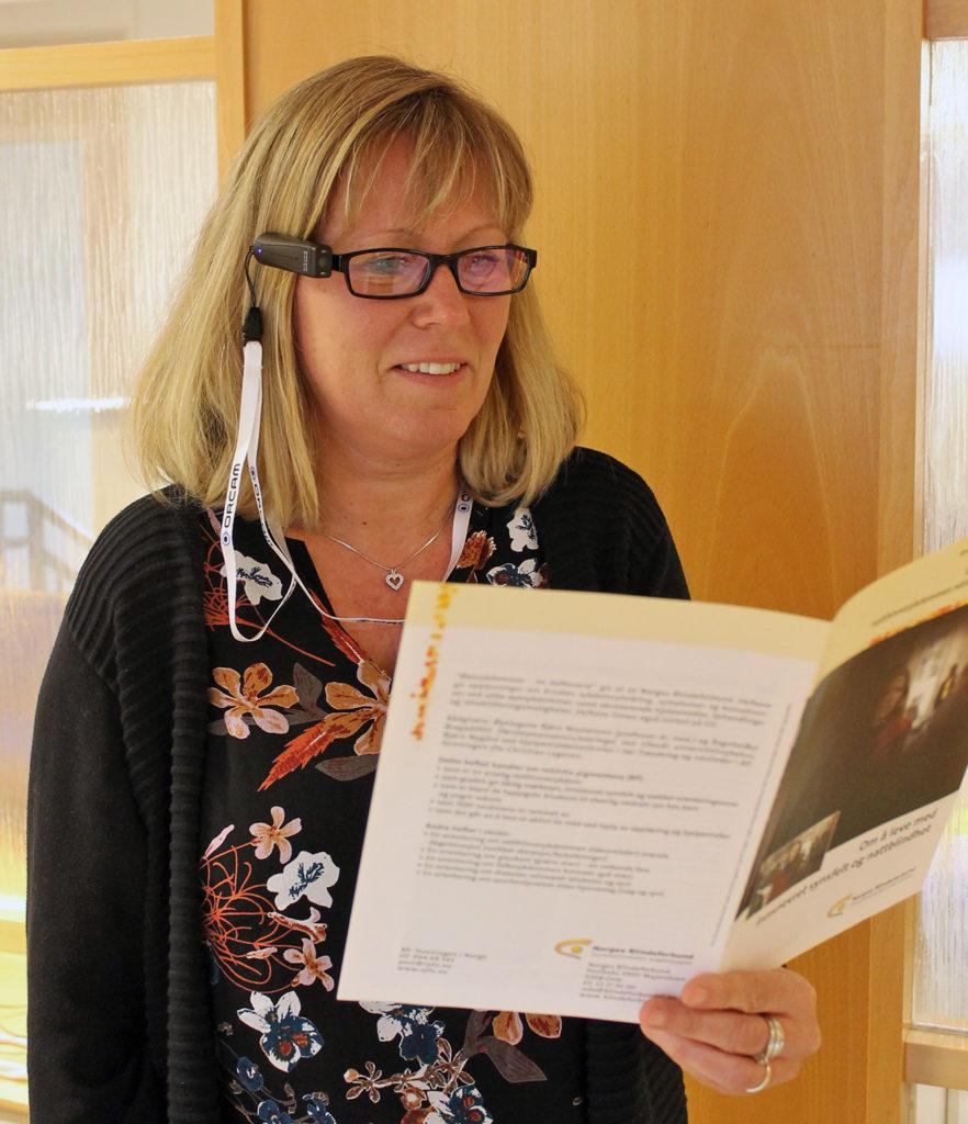 En kvinne som bruker Orcam MyEye2 for å lese fra et hefte (Foto: Jørn Stadskleiv og Hege Grimsøen)