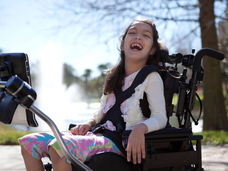 Glad jente i rullestol med sitt kommunikasjonshjelpemiddel (Foto: Tobii Dynavox)