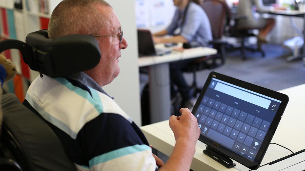Mann som bruker et høyteknologisk hjelpemiddel (Foto: Cognita)