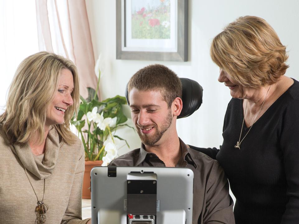 Ung mann som bruker et høyteknologisk hjelpemiddel når han kommuniserer med to damer (Foto: Tobii Dynavox)