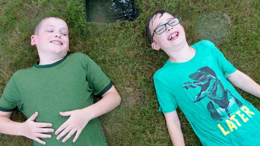 To gutter som ligger på ryggen på en plen med et nettbrett mellom seg (Foto: Tobii Dynavox)