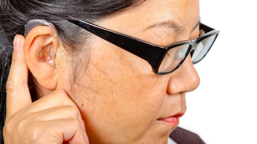 Nærbilde av dame som trykker på høreapparatet sitt (Foto: colourbox.com)