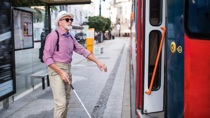 Eldre mann med mørke solbriller og blindestokk som går på bussen (Foto: colourbox.com)