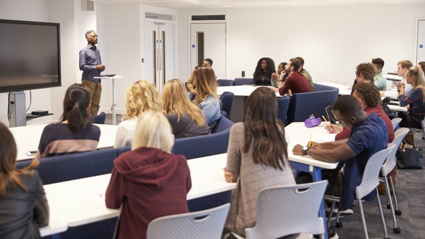 En mannlig foreleser i et klasserom foran mange studenter (Foto: colourbox.com)