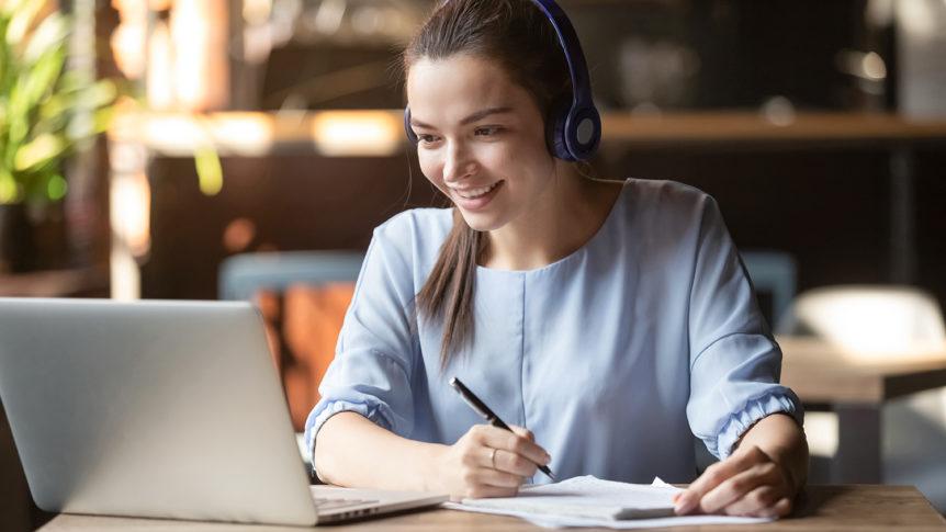Smilende ung dame med hodetelefoner som sitter foran datamaskinen og arbeider (Foto: colourbox.com)