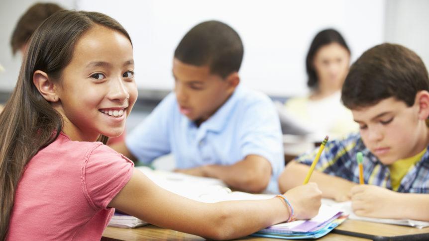 Jente med rød t-skjorte som gjør skoleoppgaver sammen med andre elever i klassserommet (Foto: colourbox.com)