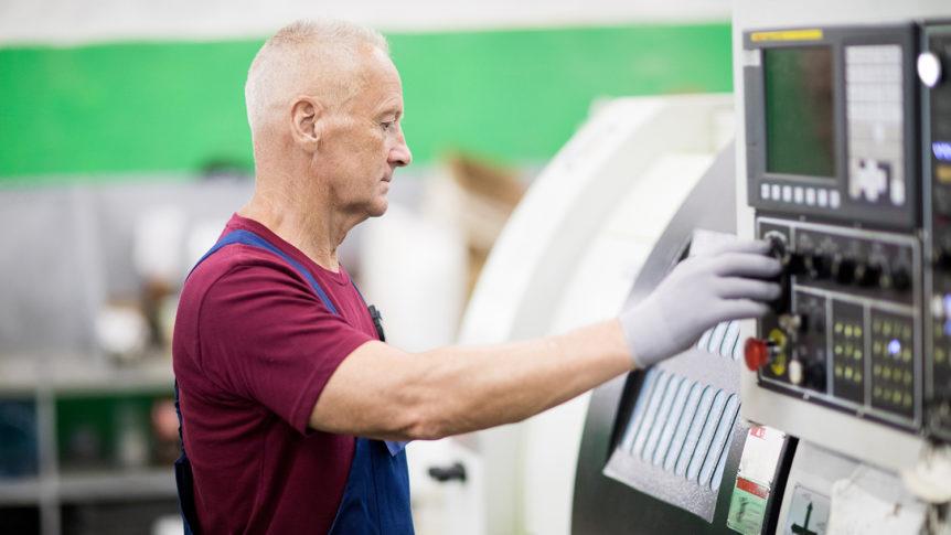 Eldre mann med grått hår som betjener en dreiemaskin (foto: colourbox.com)