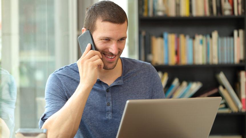 Smilende mann som snakker i telefonen mens han ser på en bærbar pc (Foto: colourbox.com)