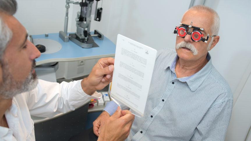 Eldre mann med testbrille som tar en lesetest hos en optiker (Foto: colourbox.com)