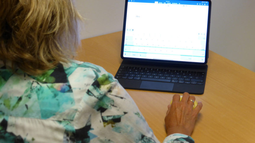 En dame som styrer iPad med en gul bryter