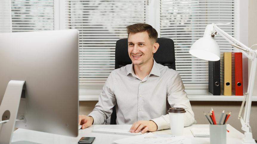Smilende mann som sitter på en kontorstol og arbeider foran dataskjermen (foto: colourbox.com)