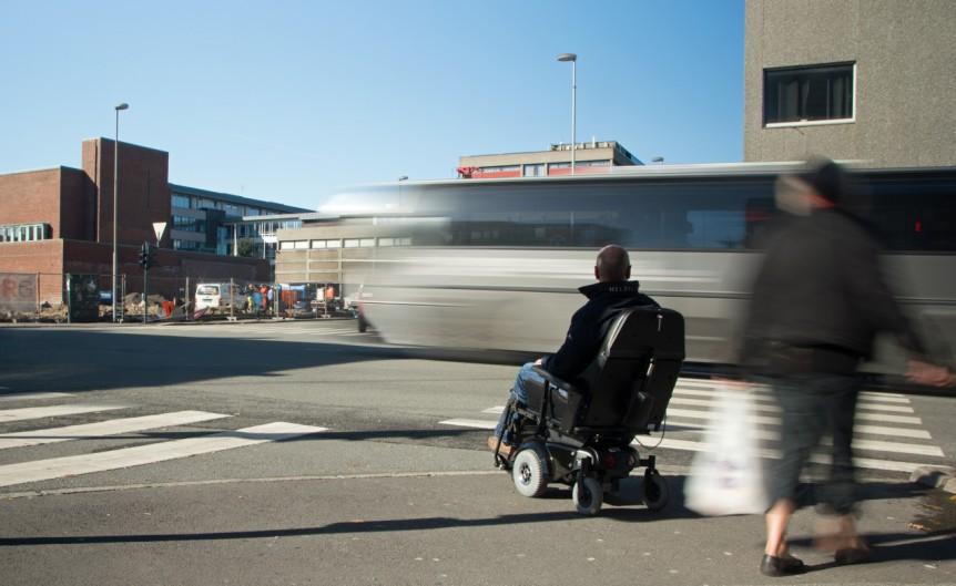 Mann i en elektrisk rullestol som har stoppet ved en fotgjengerovergang og ser en buss kjører fort forbi