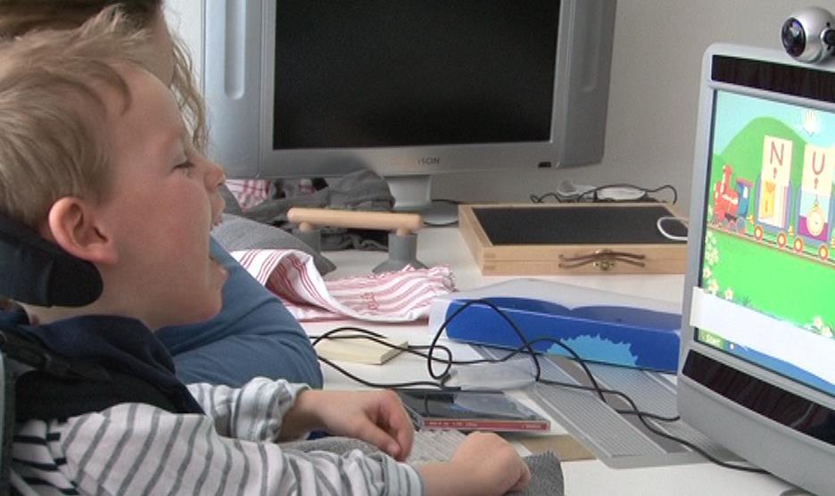 Smilende gutt i rullestol som spiller dataspill