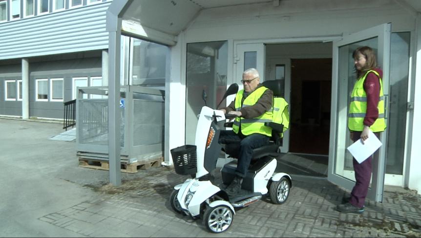 Eldre mann som prøver en rullestol mens ergoterapeuten følger med