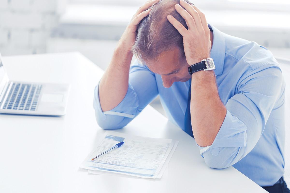 Mann som sitter foran pc-en og tar seg til hodet (Foto: Colourbox.com)