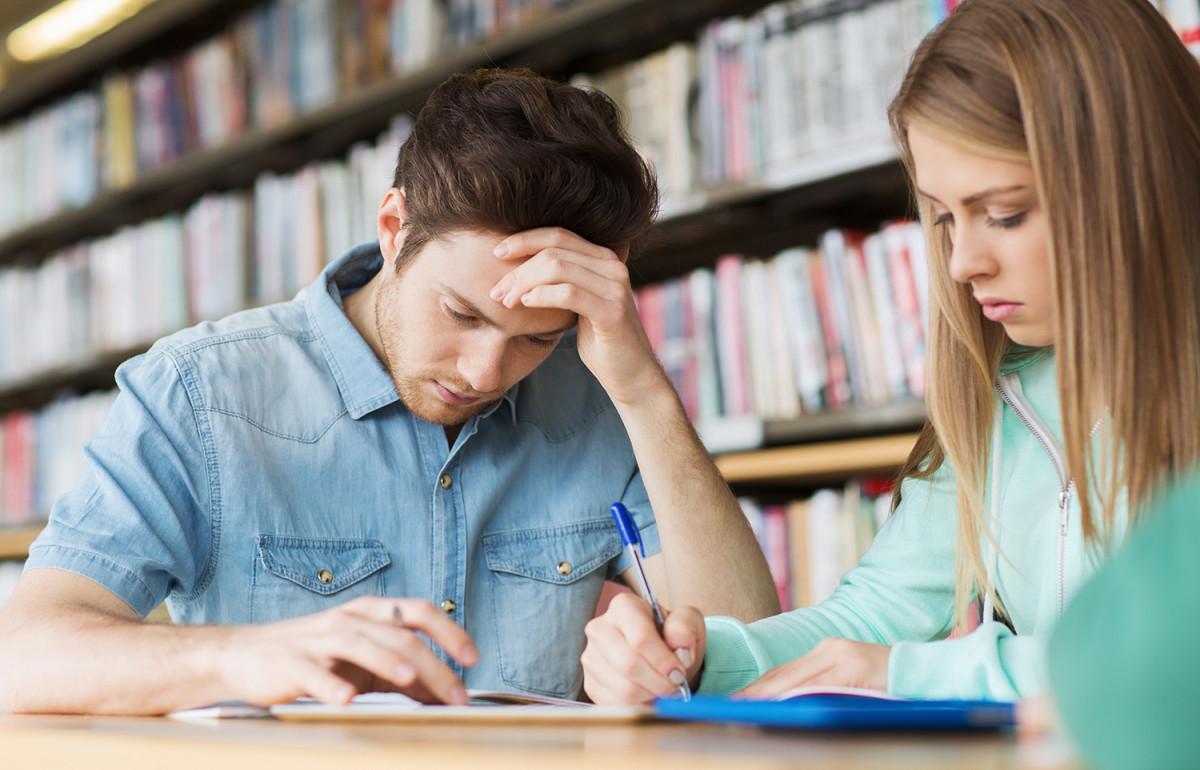 To studenter som sitter i et bibliotek og gjør notater på nettbrettet (Foto: Colourbox.com)