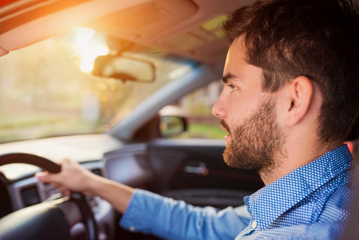 Ung mann i blå skjorte som kjører bil (Foto: Colourbox.com)