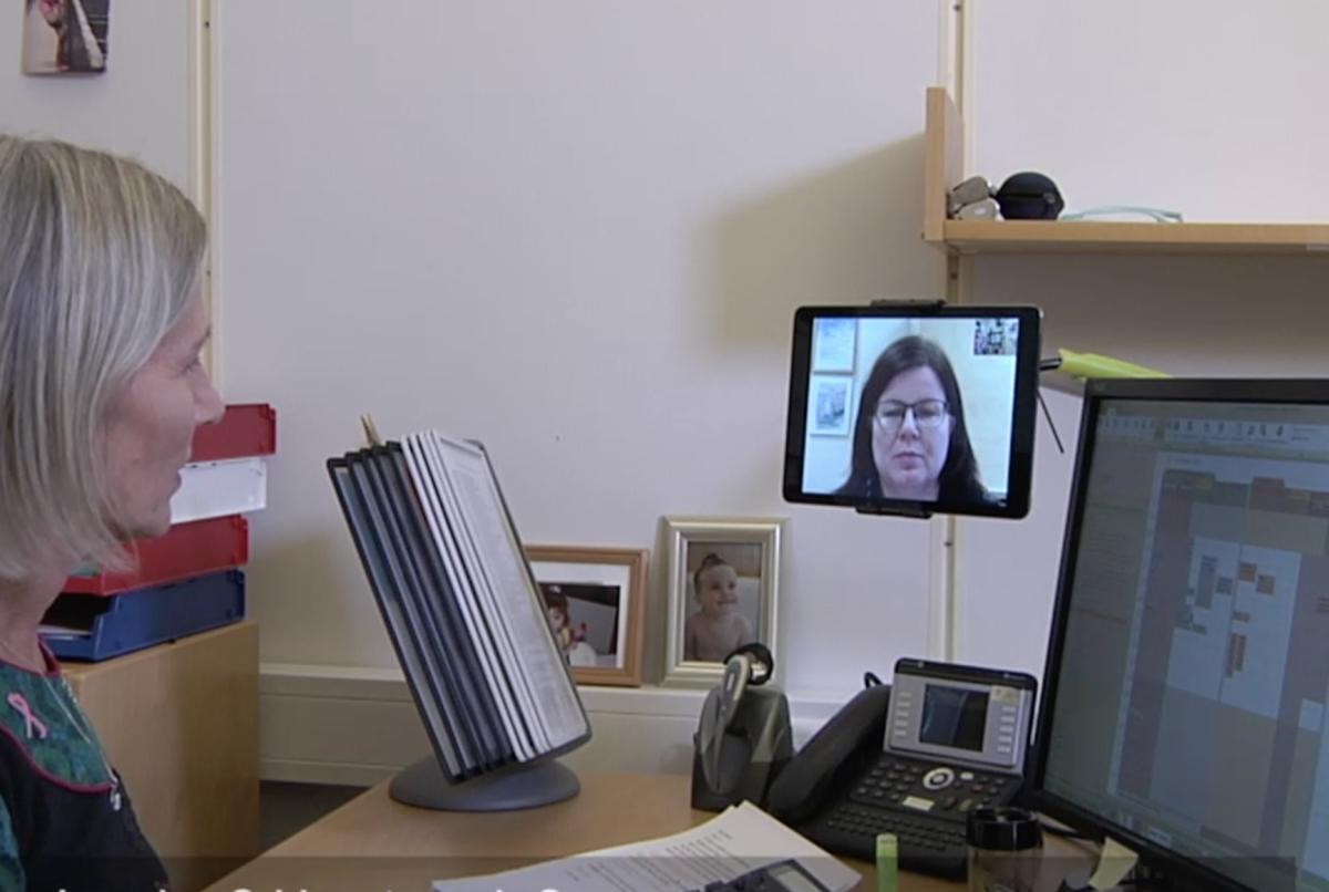 En kvinne sitter ved kontorarbeidsplassen sin og har skype-samtale