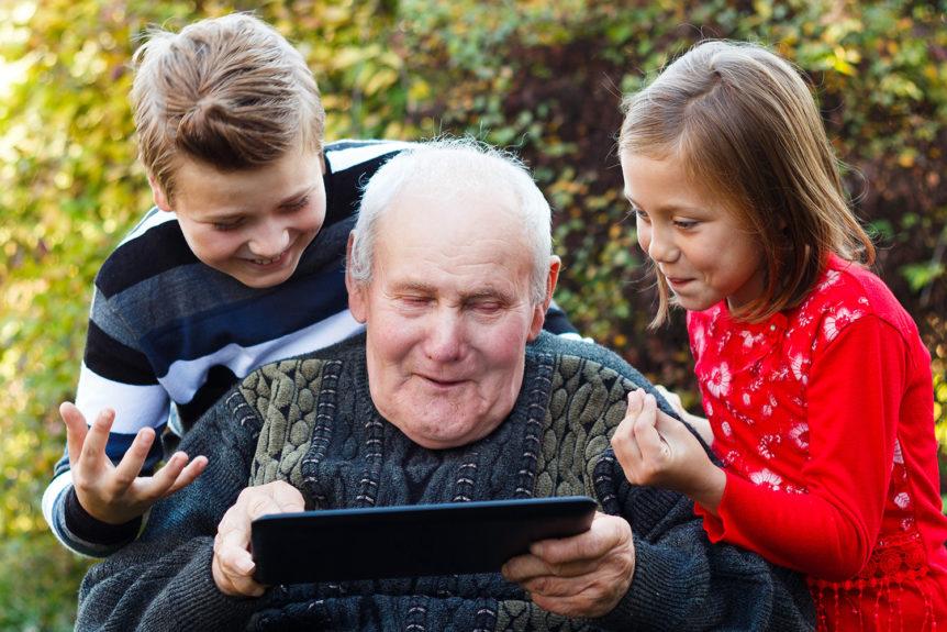 Sittende eldre mann med to barn rundt seg som viser noe på nettbrettet (Foto: Colourbox.com)