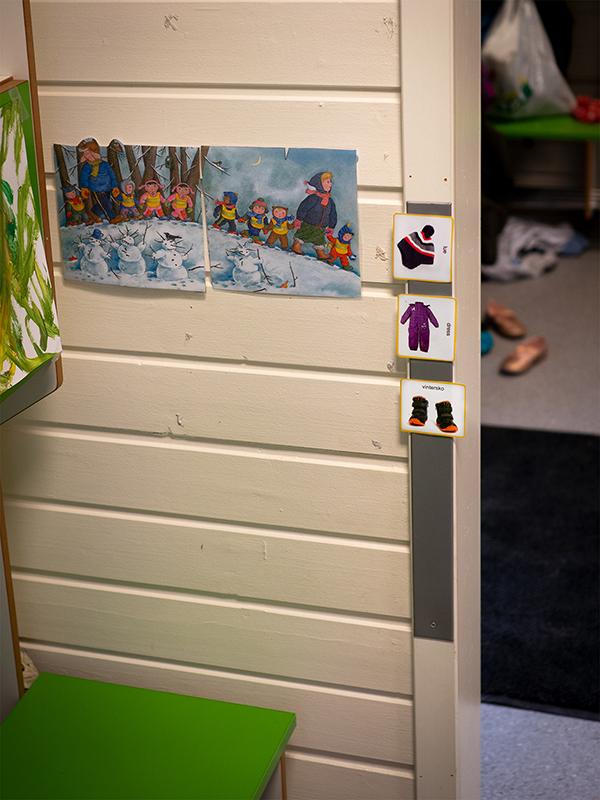 Tre kommunikasjonskort på veggen festet med borrelås