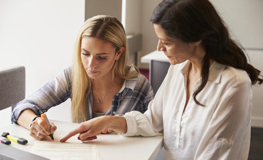 Lærer som viser elev hvordan en kan bruke markeringspenn i lesearbeidet (Foto: colourbox.com)