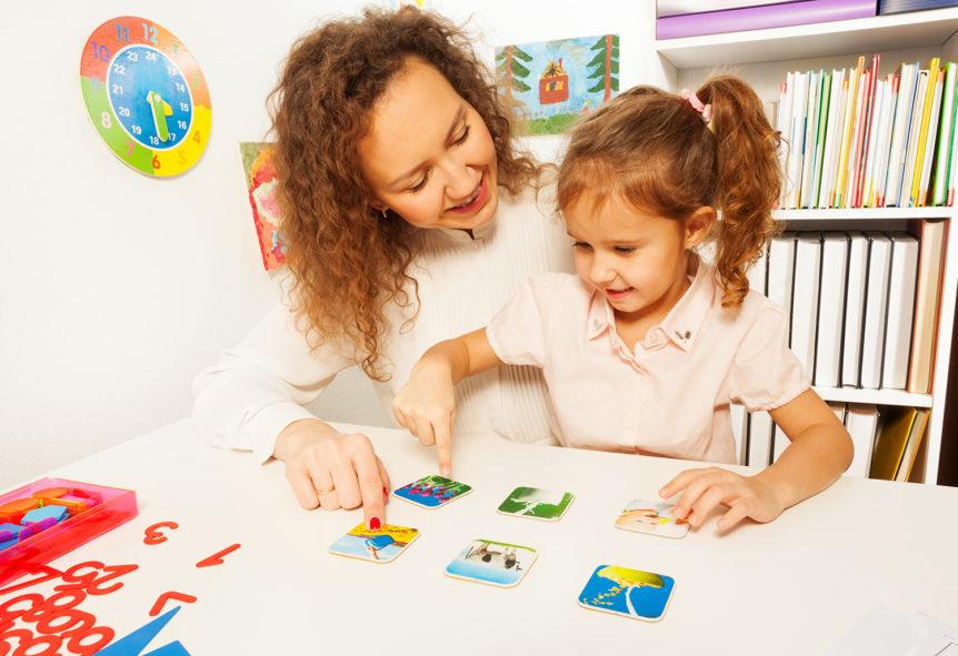 Liten jente som peker på et kort med bildestøtte (Foto: colourbox.com)