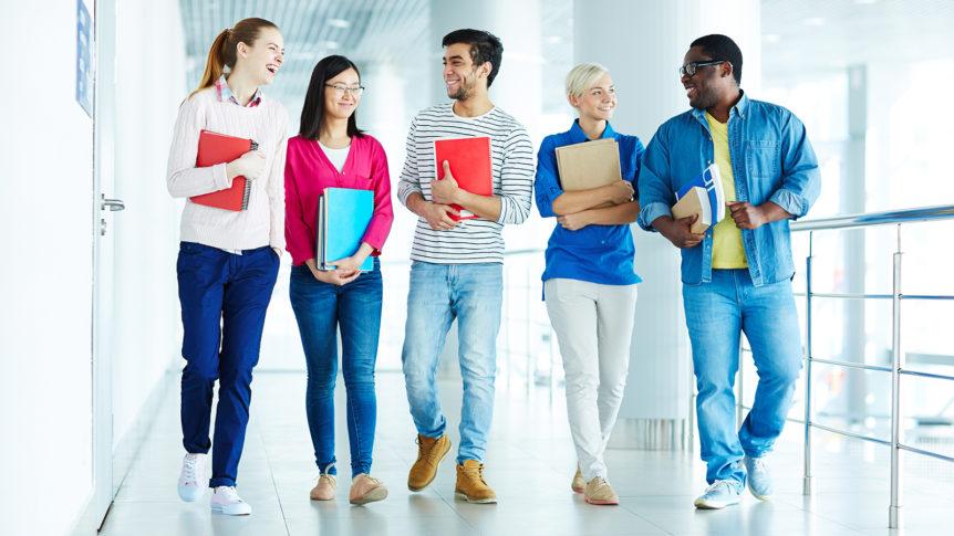 Fem smilende studenter som går i korridoren (Foto: colourbox.com)