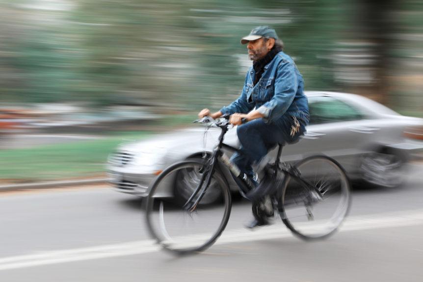 Voksen mann som sykler ved siden av en grå bil i fart (Foto: colourbox.com)