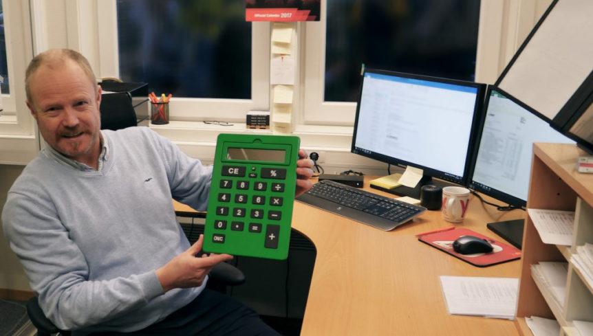 Willy Solberg viser frem den store grønne kalkulatoren han fikk av kollegaene når han begynte i den nye jobben (Foto: Silje Helen S Rygh, NAV)
