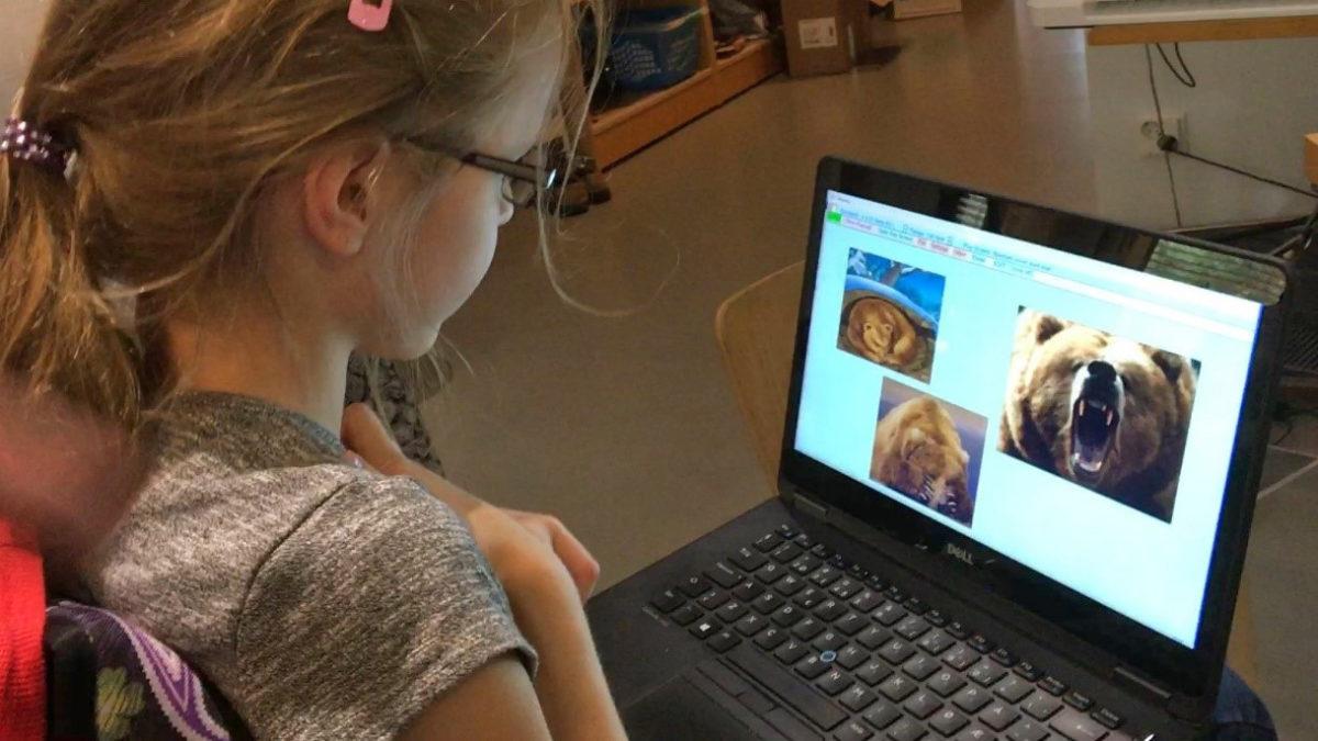 Liten jente som bruker øyestyring for å spille Bjørnsen sover på datamaskinen (Foto: SKUG-senteret, Tromsø kommune)