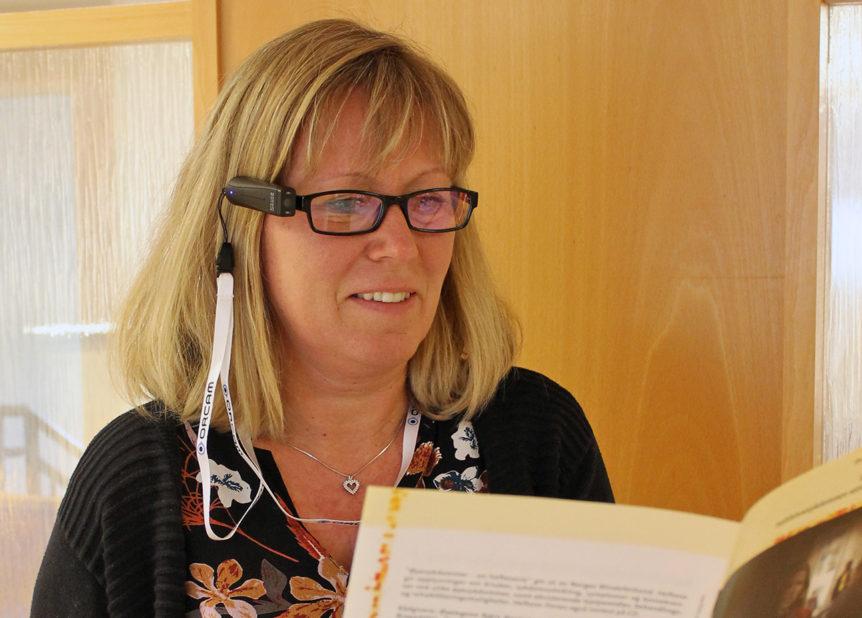 En kvinne som bruker Orcam MyEye2 for å lese fra et hefte (Foto: Jørn Stadskleiv)