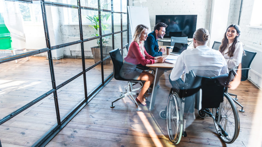 En mann i rullestol som sitter rundt et bord med tre kollegaer (Foto: colourbox.com)