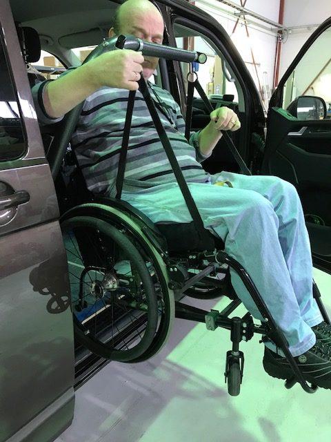 Forflytning av rullestol med bruker inn i bil med løftearmen Superarm