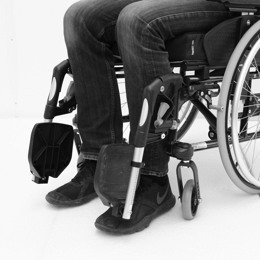 Manuell rullestol med benstøtter hvor fotplatene er vippet opp