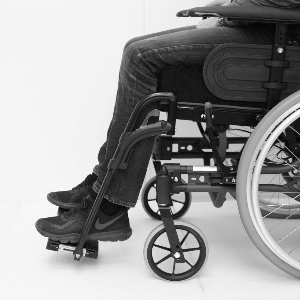 Manuell rullestol med fotbrett som er stilt for lavt for personen som sitter i den