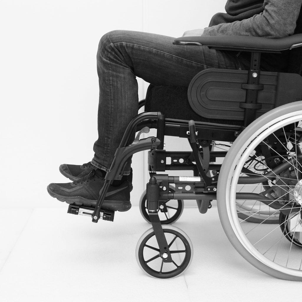 Manuell rullestol med fotplater som er stilt for høyt for personen som sitter i den