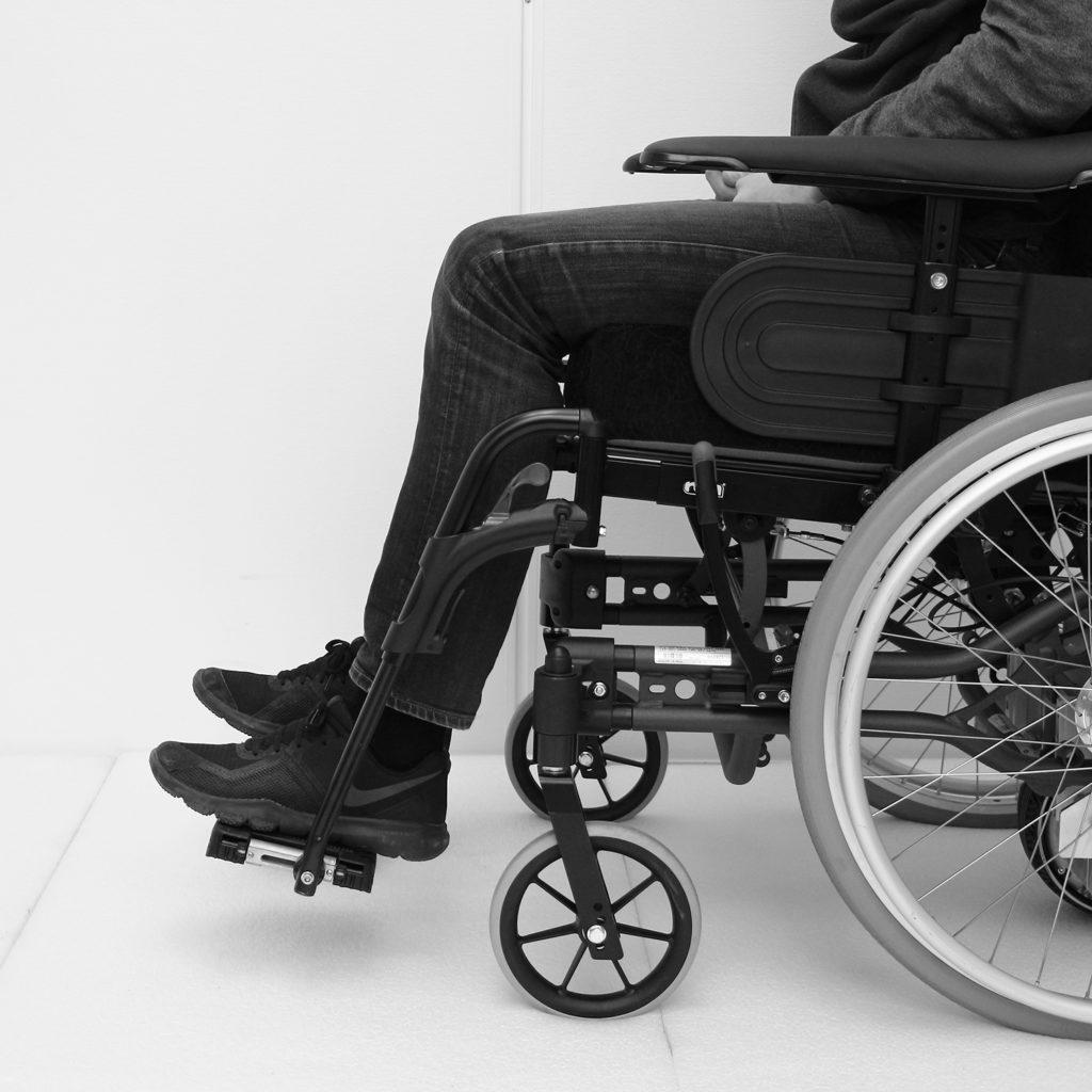 Manuell rullestol med riktig innstilt høyde på fotbrett for personen som sitter i den