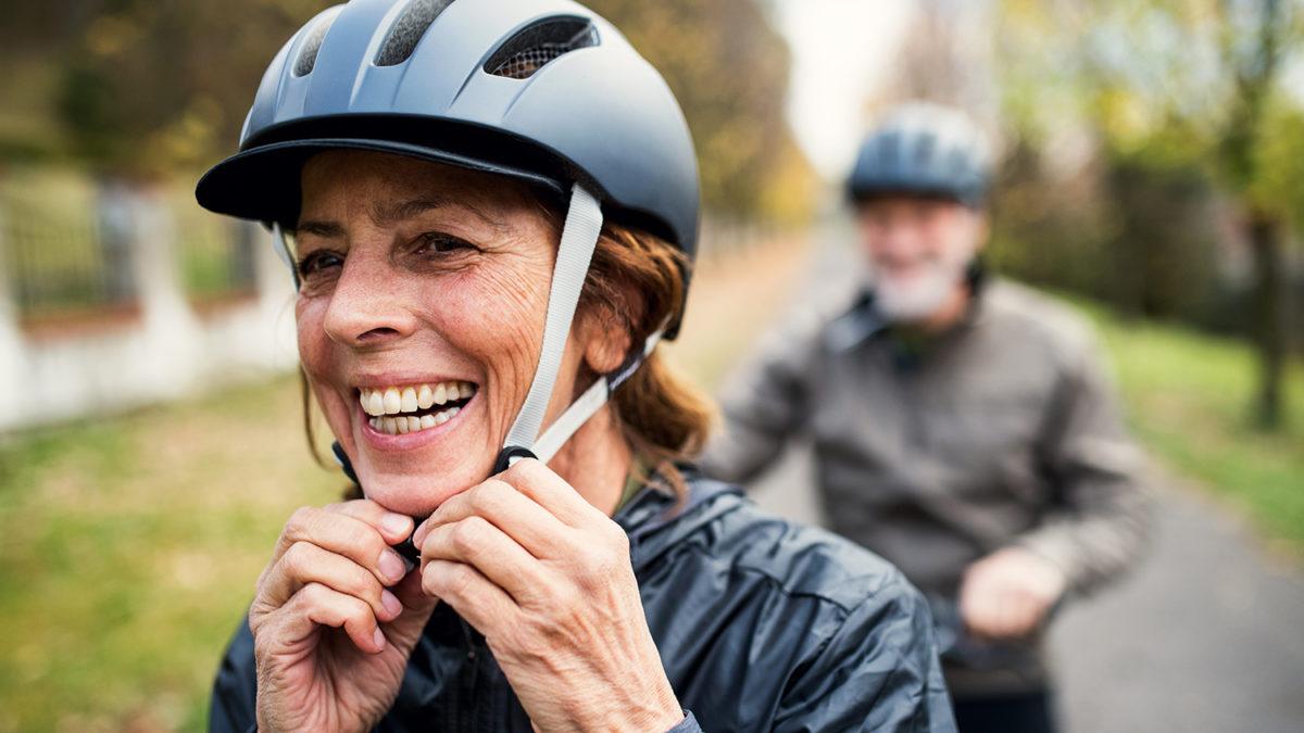 Voksen kvinne som fester stroppen til sykkelhjelmen (Foto: colourbox.com)
