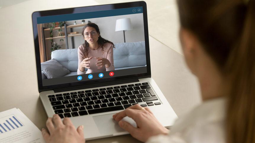 En kvinne med ryggen til sitter foran en bærbar pc og har videomøte med en annen kvinne (Foto: colourbox.com)