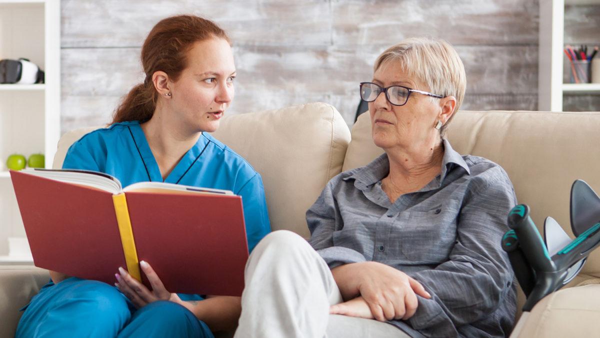 En kvinnelig pleier og en voksen dame som sitter i en sofa og ser på et fotoalbum (Foto: colourbox.com)