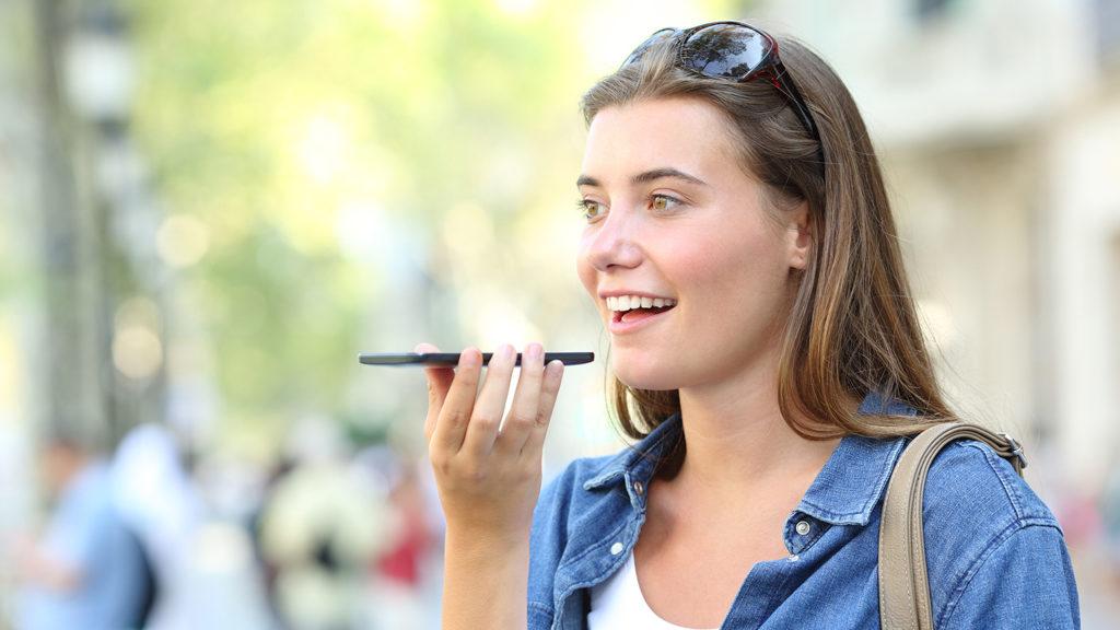 Blid jente på gata som bruker talestyring på mobilen (Foto: colourbox.com)